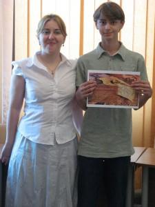 """Cristian Cazacu primind titlul de ,,Cel mai tanăr cartograf""""'  diplomă înmanată de către Decanul Facultăţii de Geografie, doamna conf. univ. dr. Laura Comănescu."""